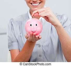 Charming woman presenting a piggybank