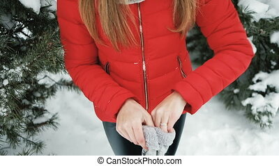 charming woman puts on mittens to get warmed on winter wind...