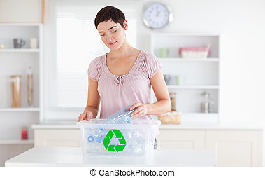 Charming Woman putting bottles in a recycling box
