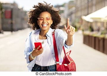Charming woman raising her finger and using phone