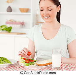 Charming woman ready to eat a sandwich for lunch in her ...