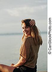 Charming woman sitting on beach