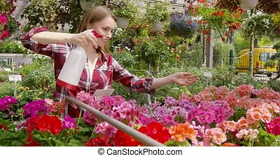 Charming woman spraying flowers in garden - Young woman in...