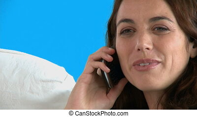 Charming woman talking on phone sitting against a blue...