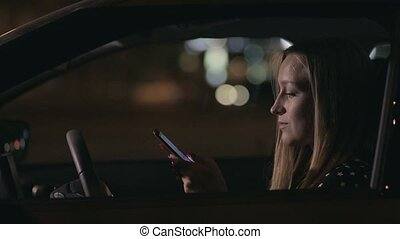 Charming woman texting message on cellphone in car