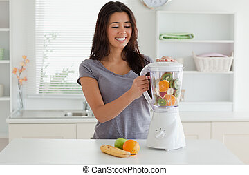 Charming woman using a blender while standing