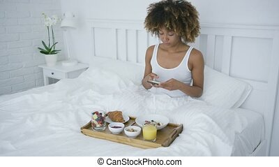 Charming woman using phone while having breakfast - Pretty...