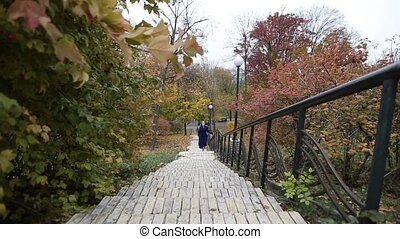 Charming woman walking up the stairs in fall - Attractive...