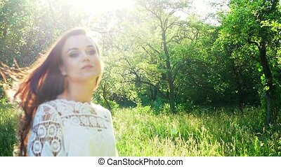 Bright Sunny Day In The Park And Lovely Woman Bathing In The Sunlight. Slow Motion Of Attractive Young Girl Standing In The Sunlight Outside.