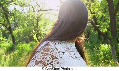 Cheerful Woman Walks Backwards And Smiles. Slow Motion Of Pretty Young Girl Pushing Her Hair, Smiling And Heading Forward. Charming Woman Flirts And Proposes To Follow Her. Follow-Me Concept