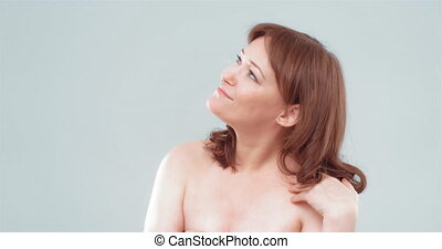charming woman with naked shoulders tidying her hair close-up shot, spa and wellness concept. Woman applying anti-age cream on her skin isolated on white background. Prores 422.