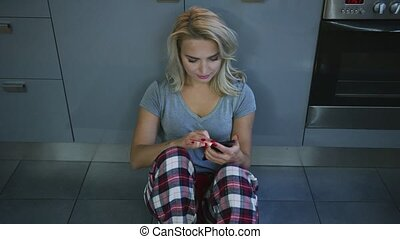 Charming woman with smartphone on kitchen floor - Beautiful...
