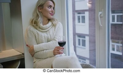 Charming woman with wine sitting near window