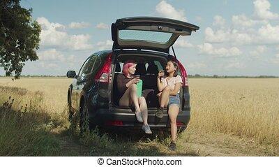 Charming women having coffee break during road trip -...