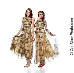 Charming women posing in dresses from same cloth