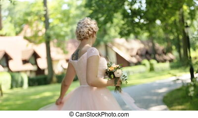 Charming young blonde bride with bouquet in romantic lace wedding dress dancing at sunset in park. Ideas for stylish rustic forest wedding