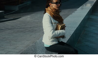charming young brunette in glasses with books in hands sits in the street