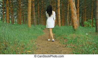 young brunette in white derss walks on the footpath in the forest