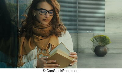 Charming young brunette student reading a book in the street
