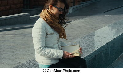 charming young brunette woman reading a book in the street