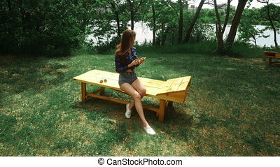 young brunette woman sits outdoors and surfing internet with mobile phone at the park