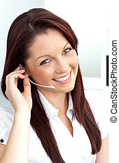 Charming young businesswoman wearing headphones smiling at the camera in her office