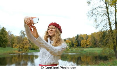 Charming young Caucasian woman in a little red riding hood posing and taking a selfie on your modern smartphone and smiling in autumn Park.