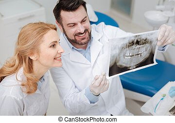Charming young dentist sharing the progress of his patient