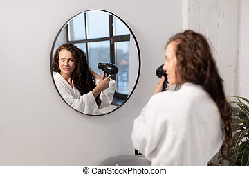 Charming young female with hair-dryer taking care of her dark long wavy hair