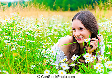 charming young girl in a field with lush grass