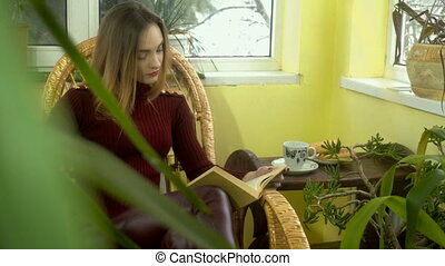 charming young girl reading a book in a wicker rocking chair near the window with lots of green plants around