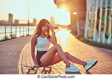 Charming young hipster girl posing while sitting on a skateboard at the embankment during beautiful sunset.
