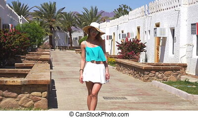 lady in straw hat and sunglasses posing on camera with clothes fly in the wind