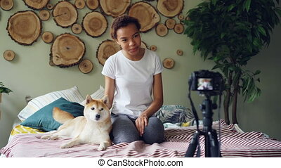Charming young lady is recording video about pet dogs,...