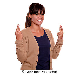 Charming young woman crossing her fingers for luck