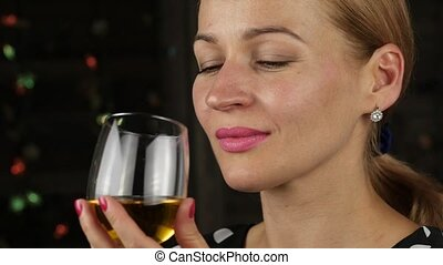 charming young woman drinking white wine in a dark. close-up...