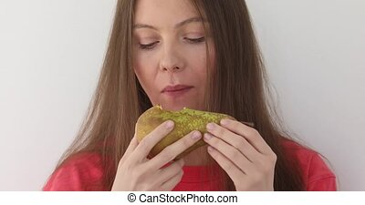 Charming young woman eats a green pear and smiles