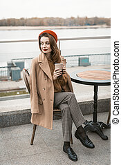 Charming young woman having a coffee sitting at empty restaurant terrace holding a coffee mug, wearing red beret. Autumn urban city on background.