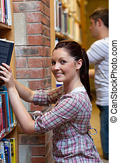 Charming young woman looking for a book