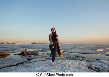 Charming young woman near the river with ice at spring.