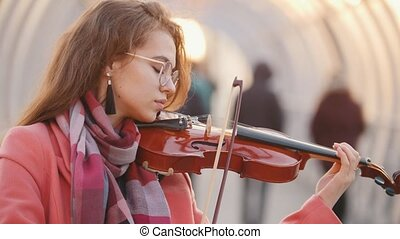 Charming young woman playing violin for free in public, mid...