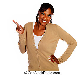 Charming young woman pointing right looking at you