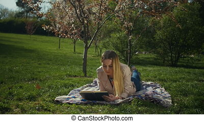 Charming young woman reading a book in spring park