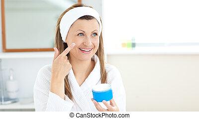 Charming young woman using cream wearing a bath robe