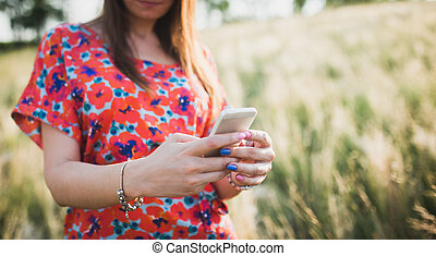 Charming young woman using to mobile smart phone, against green