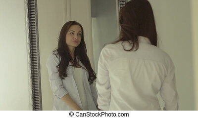 Charming young woman with long healthy hair,in white shirt and jacket admiring herself in the mirror.