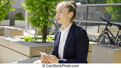 Charming young woman with smartphone outside