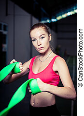 Charming young woman workout with rubber bands at fitness gym.