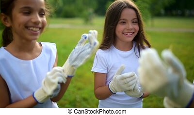 Charming youngsters getting ready for cleaning outdoors -...