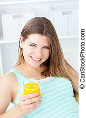 Charmingl young woman holding a glass of orange juice ...
